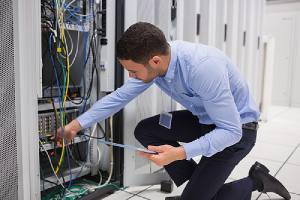A managed IT services professional checking plugin cables into server in data center