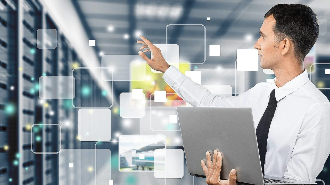 A representational image of Managed IT services. A person holding a laptop is standing on the backdrop of a data center