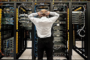 a man looking at server racks after a disaster affected his business