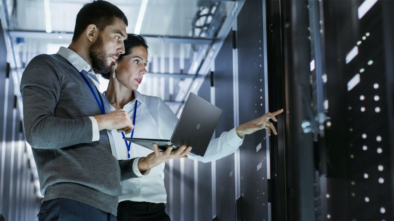 two employees monitoring a data center after a secure network installation