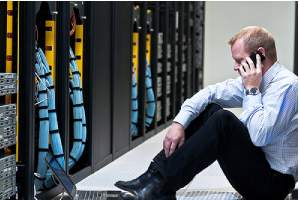 A worried technician in a Data storage center.Disaster Recovery is important for Business