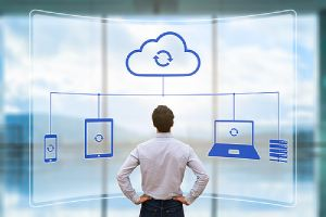 An illustration of cloud synchronizing between devices as a person looks up data backup to help protect their businesses