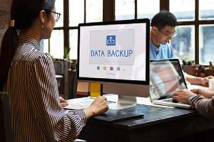 woman sitting at her computer with the words data backup on her screen showing a cloud network data backup concept