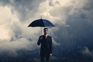 a man with umbrella standing over stormy background. Make disaster recovery plan a top priority