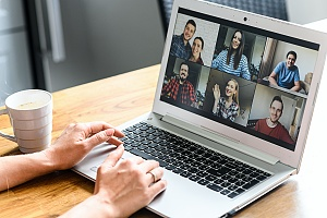 person sitting at a table in a meeting while working remotely