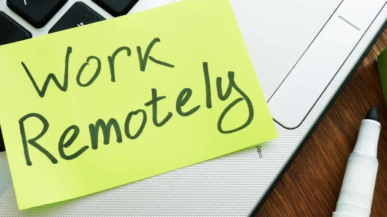 yellow sticky note on a laptop with the words work remotely written on it.jpg
