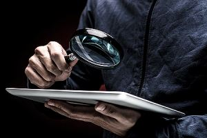 Man holding a magnifier depicting cyber security threat. A network security assessment is a must for every business