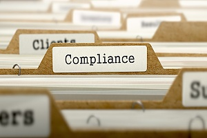 the word compliance on a file in a file cabinet
