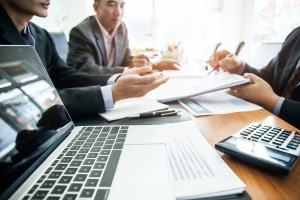 computer on table with men finding out exactly What Is IT Consulting