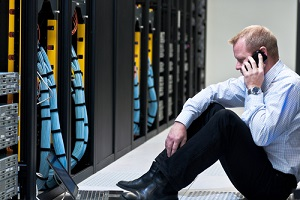 man calling on a smartphone and looking at a laptop computer in a network data center