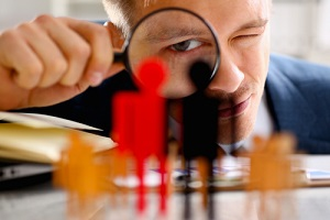 man in suit look thru loupe on statuettes closeup in office