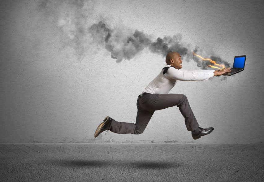 man running with a burning laptop