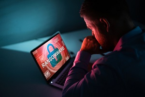 businessman looking at laptop with ransomware
